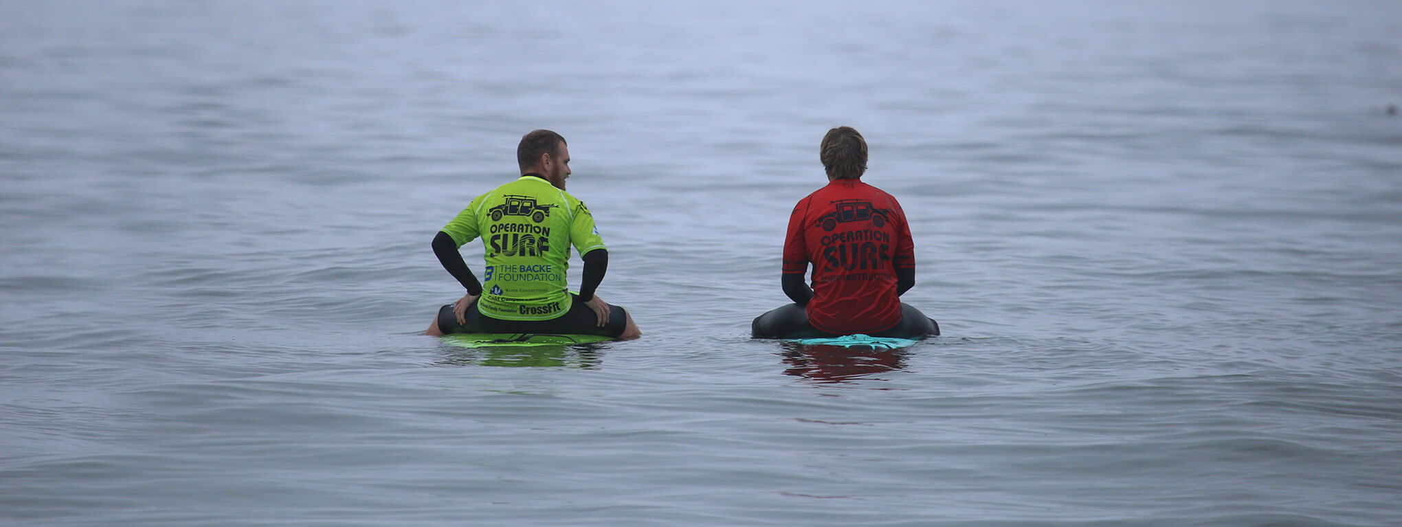 Instructor and participant float on surfboards