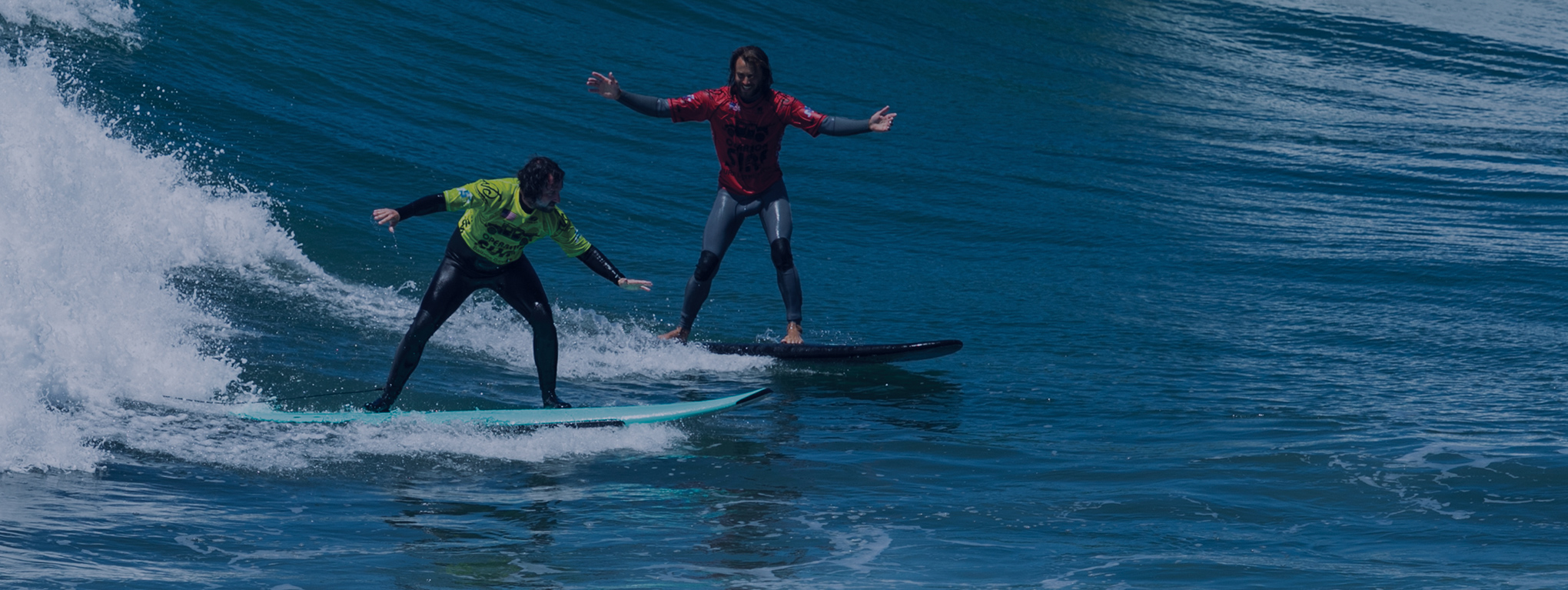 Two Operation Surf participants ride a wave