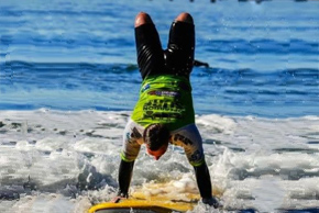Michael E., USMC does a handstand on his surf board
