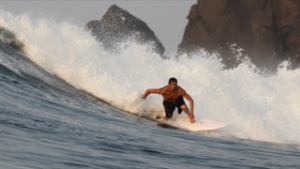 Instructor Richard Rodriguez rides a wave