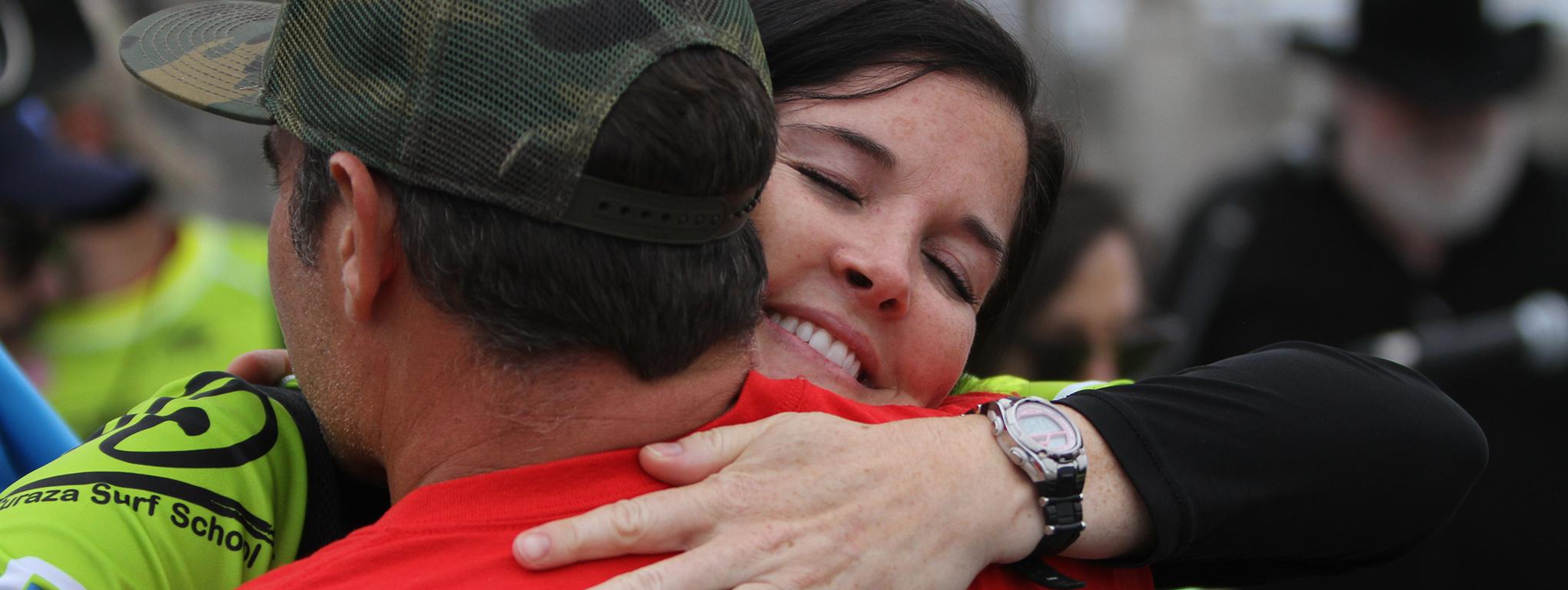 A volunteer hugs a participant