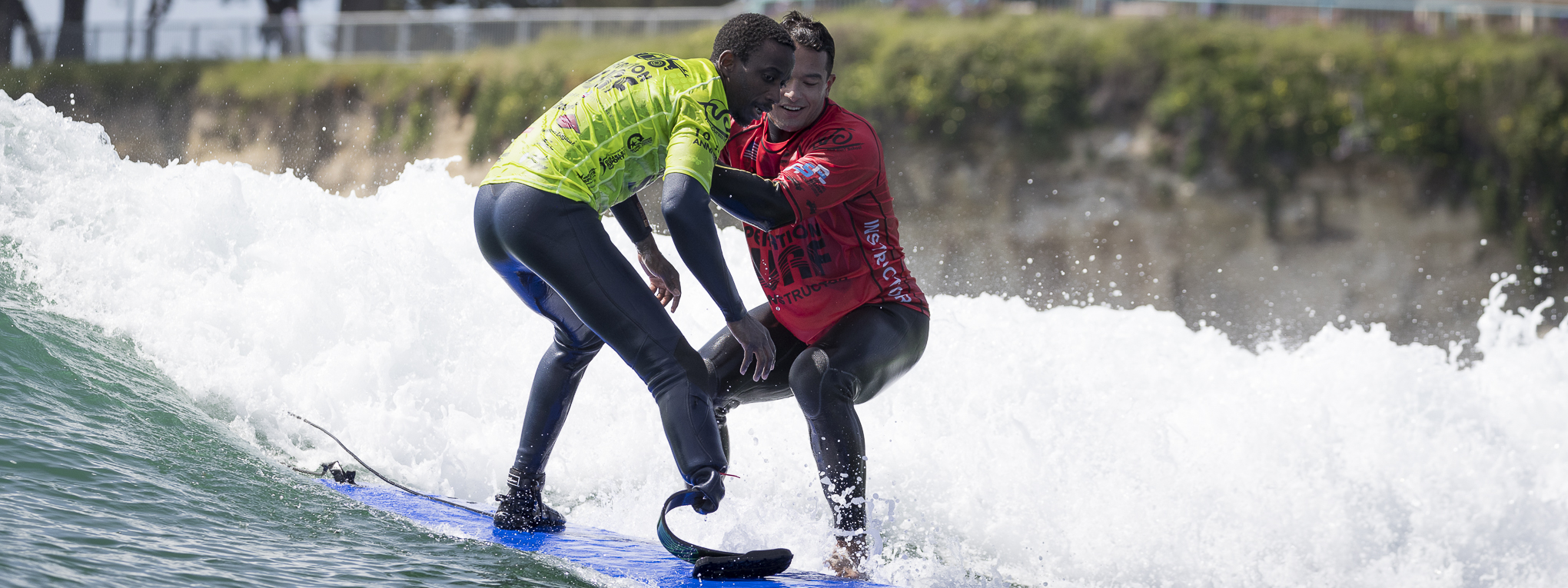 Surf instructor helping a military veteran