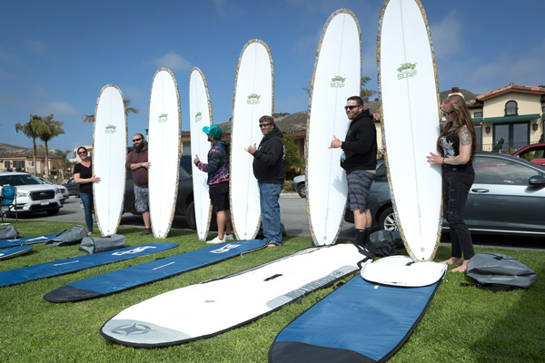 6 people holding up surf boards.
